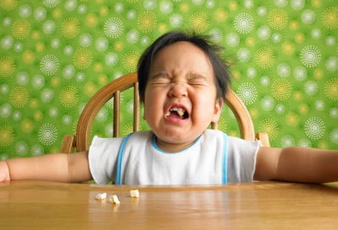 Baby boy crying in highchair at table