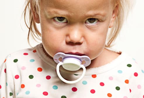Intense young girl with pacifier in mouth