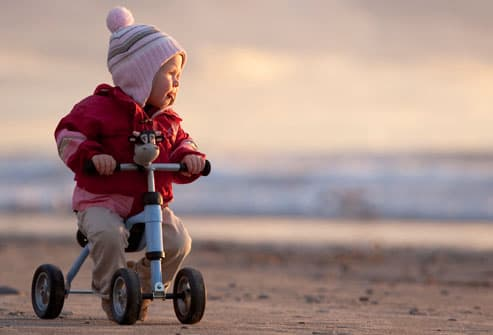 Infant girl riding four wheel toy by herself