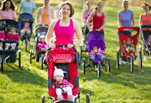 Mothers with jogging strollers in grass