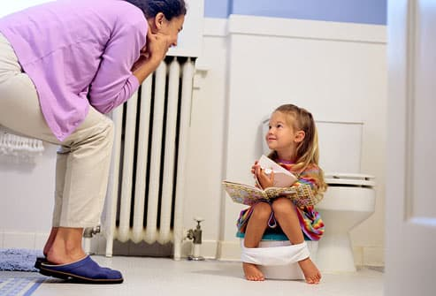 Mother watching as girl sits on potty