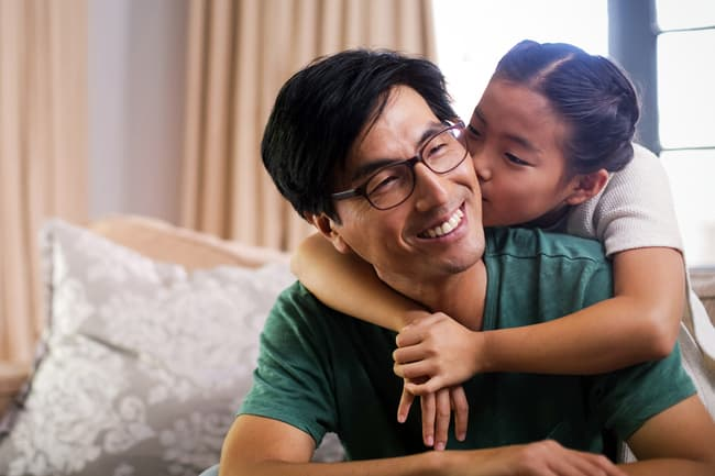 young daughter kissing father