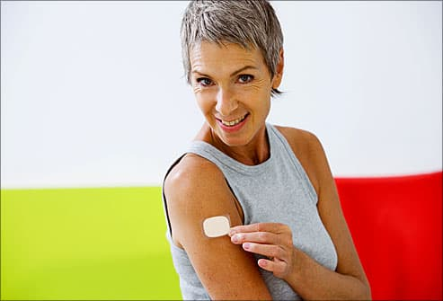 Mature woman applying nicotine patch