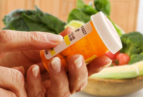 Close up of woman holding prescription bottle