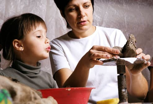 Mother sculpting clay with daughter