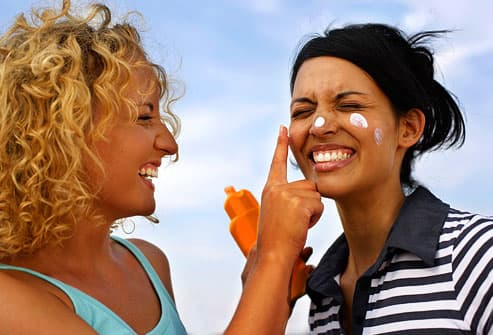 Women applying sunscreen