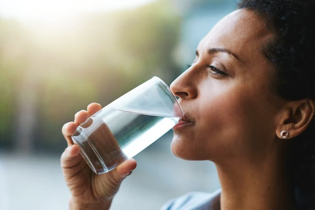 photo of woman drinking water