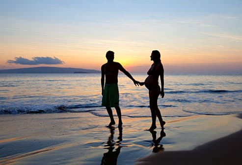 Man with pregnant wife on beach at sunset