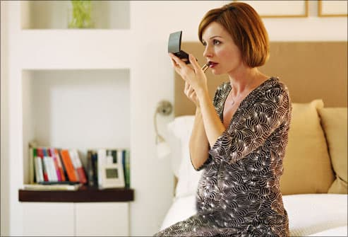 Pregnant woman checking her makeup in mirror