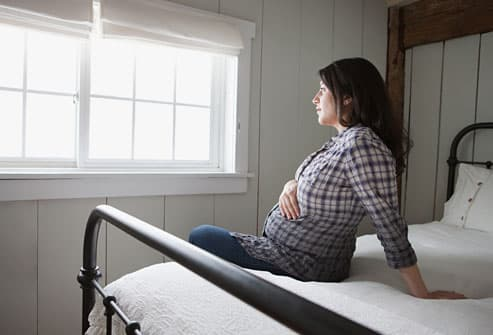 Pregnant woman looking pensively out window