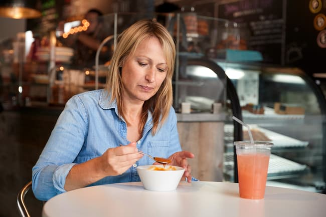 photo of woman eating soup