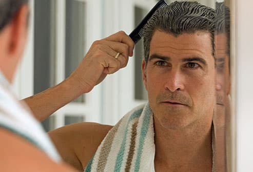 Mature man combing his hair