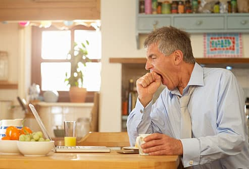 Man yawning at kitchen table