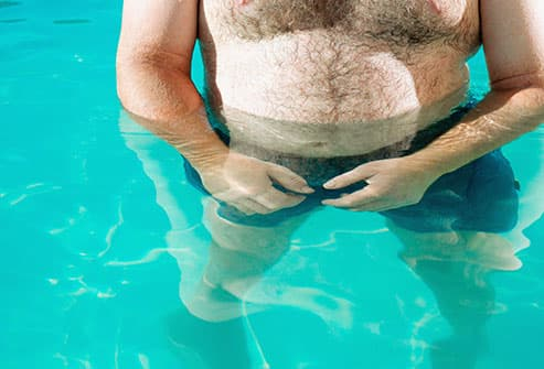 Overweight man in swimming pool