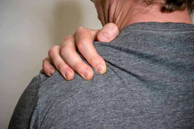 photo of person gripping shoulder