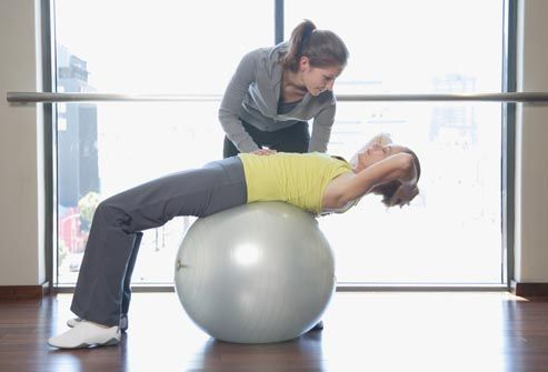 woman on exercise ball with trainer