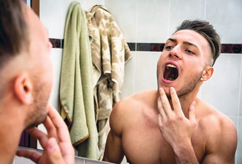 man checking mouth in mirror