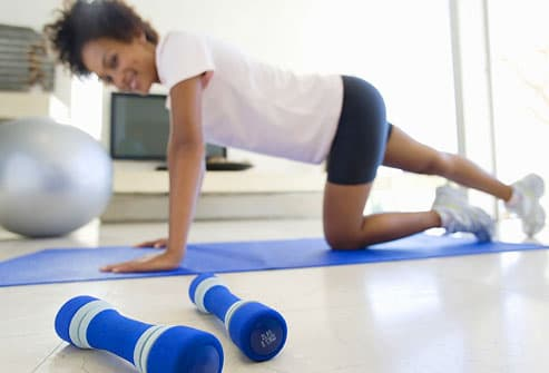 woman stretching on floor mat in living room