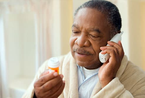 man holding prescription bottle, talking on phone