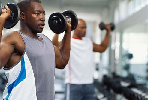 Two men exercising in a gym with dumbbells