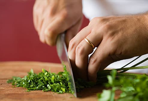 Person chopping parsley on cutting board