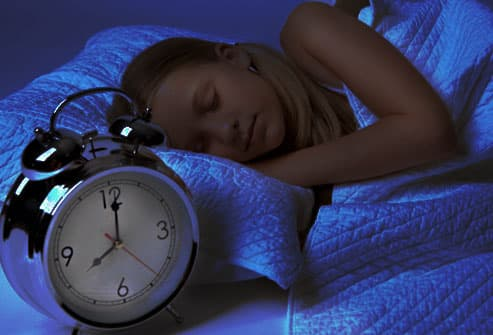 Girl asleep in bed next to clock