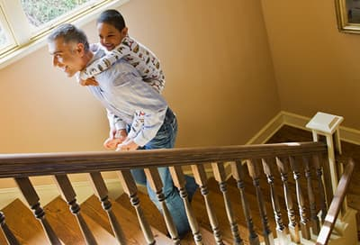 Father carrying son upstairs in pajamas
