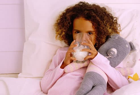 Girl drinking milk in bed