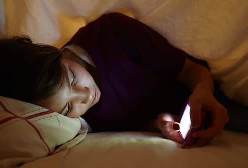 Teen girl lying in bed with cell phone