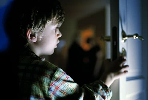 Boy opening door to parents bedroom late night