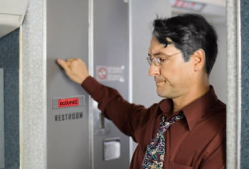 passenger knocking on lavatory door on airplane
