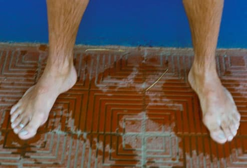 feet of man standing by pool