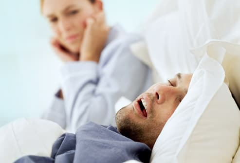 woman trying to shut out sound of snoring husband