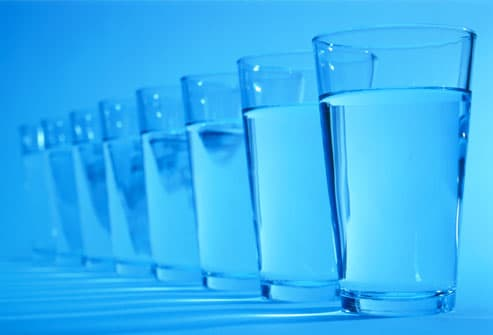 Row of glasses containing water (blue tone)