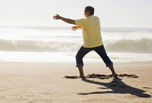 Man doing Tai Chi on beach