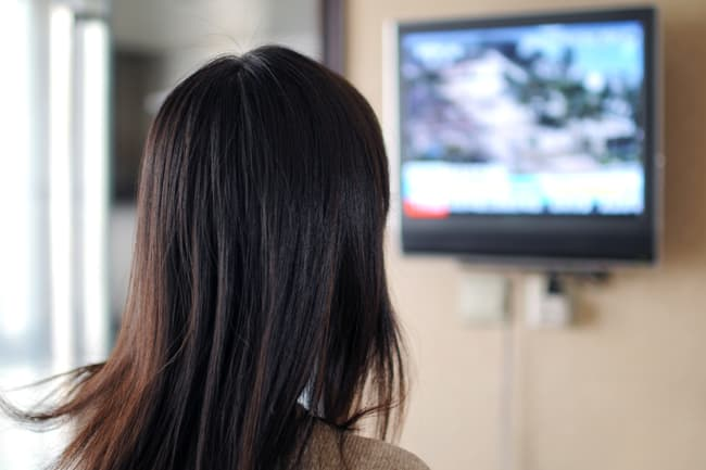 photo of woman watching tv news