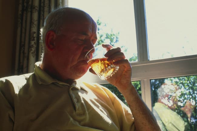 photo of man drinking alcohol at home