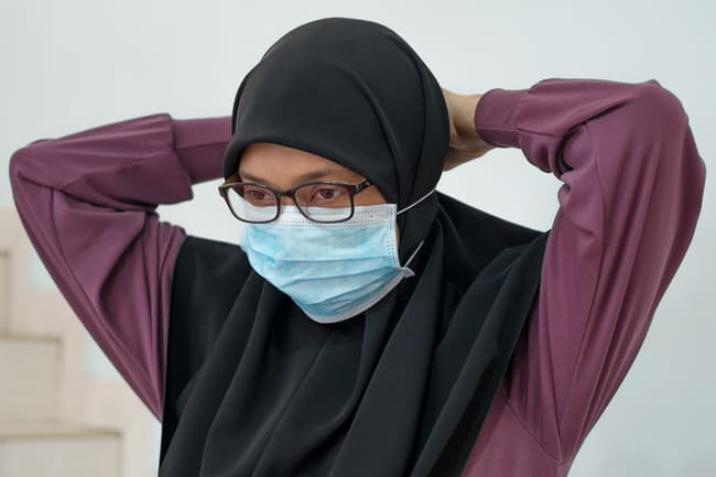 photo of putting mask over hijab