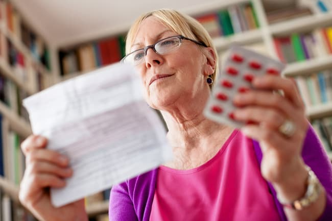 photo of woman reading medication instructions