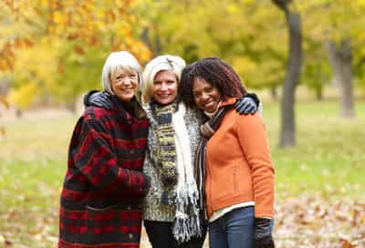 Three women standing in park, smiling