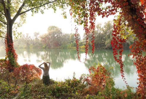 Woman looks across river from autumnal bank