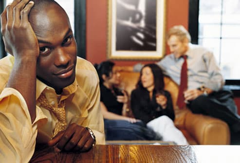 Balding young man feeling isolated in nightclub