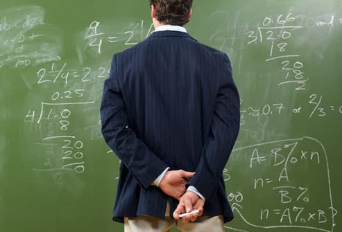 Man Looking at Math Problems on Blackboard