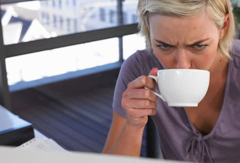 Tired looking woman drinking coffee