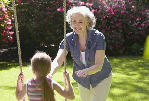 grandmother pushing granddaughter on swing