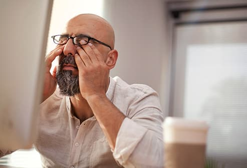 mature man rubbing eyes