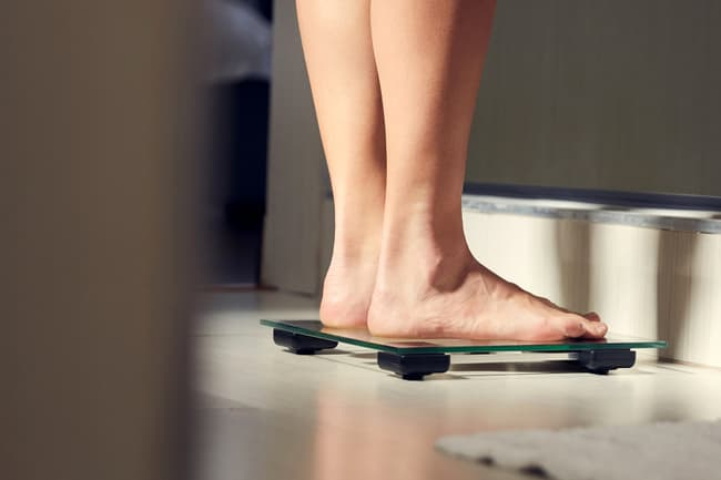 photo of woman's feet on weight scale