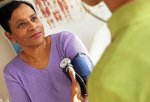 Mature woman having blood pressure checked
