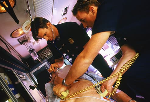 EMTs using a defibrillator on a mature man