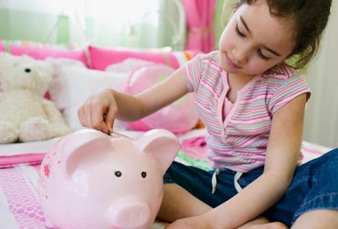 girl using piggy bank